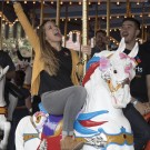 Community Leaders Ride King Arthur Carrousel for Charity